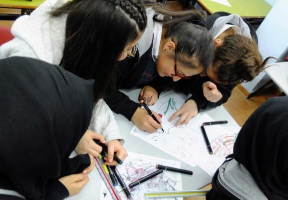 Girls working on designing a school
